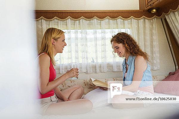 Zwei Freundinnen sitzen in einem Wohnwagen und amüsieren sich.