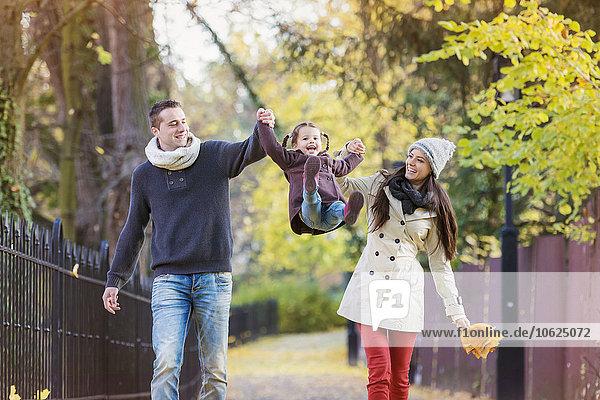 Eltern erheben Tochter im Herbstpark
