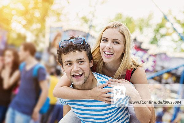Glückliches Paar auf dem Jahrmarkt  Mann trägt Frau Huckepack