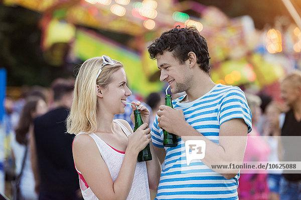Fröhliches Paar auf der Kirmes beim Trinken von Erfrischungsgetränken