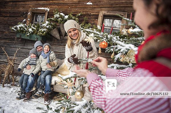 Österreich  Altenmarkt-Zauchensee  Familie schmückt Weihnachtsbaum vor dem Bauernhaus