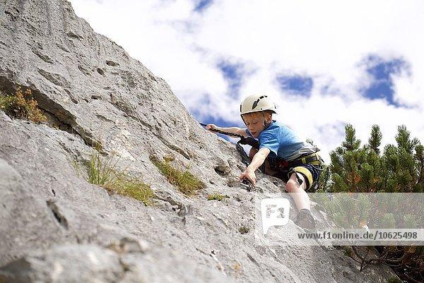 Austria  Tyrol  Rofan mountains  young boy climbing