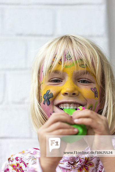 Portrait of smiling blond girl with painted face holding balloon