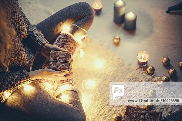 Frau sitzend mit Weihnachtsgeschenk und Lichterkette auf dem Teppich