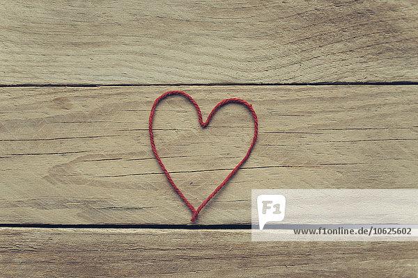 Herzform aus rotem Faden auf Holz