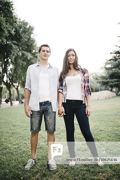 Young couple in love standing on a meadow in a park holding hands