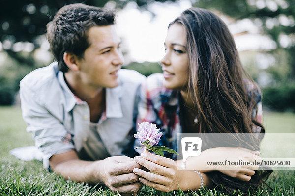 Verliebtes junges Paar liegt auf einer Wiese in einem Park und schaut sich an.