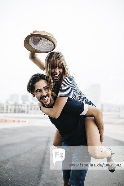 Spanien  Barcelona  junger Mann  der seine Freundin huckepack fährt