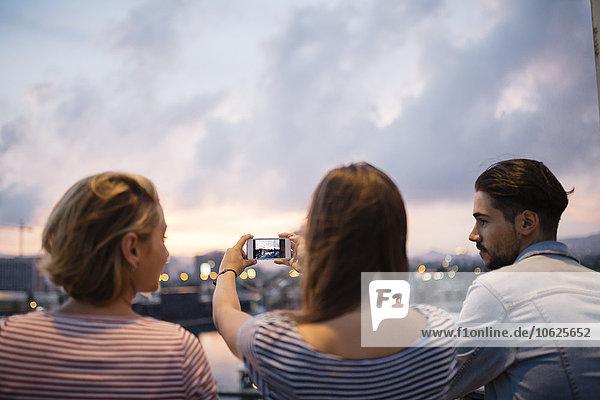Spanien  Barcelona  Rückansicht von drei Freunden beim Fotografieren mit dem Smartphone