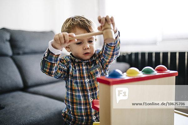 Kleiner Junge spielt mit hölzernem Motorspielzeug