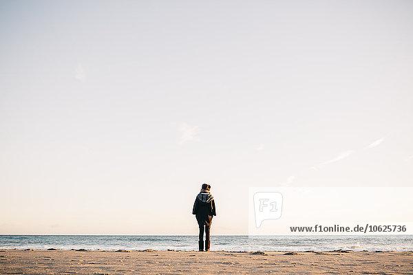 Rückansicht der jungen Frau am Strand im Winter