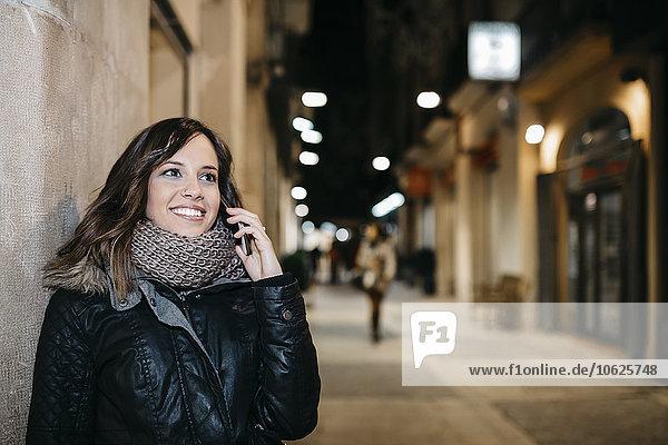Spanien  Reus  Porträt einer lächelnden jungen Frau beim Telefonieren mit dem Smartphone bei Nacht