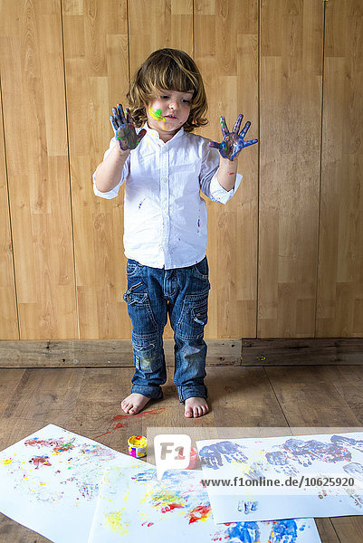 Portrait of creative little boy with palms full of finger colours