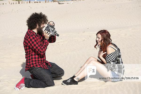 Spanien  El Puerto de Santa Maria  junger Mann beim Filmen seiner Freundin am Strand