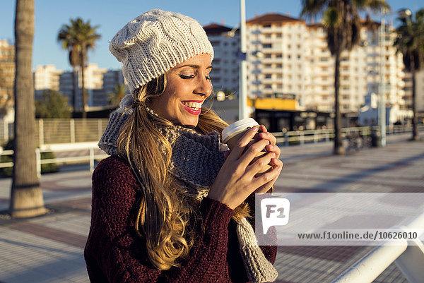 Spain  Andalusia  Cadiz  El Puerto de Santa Maria  woman in winter clothes drinking coffee