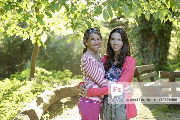 Porträt von Mutter und Tochter  die sich in der Natur umarmen