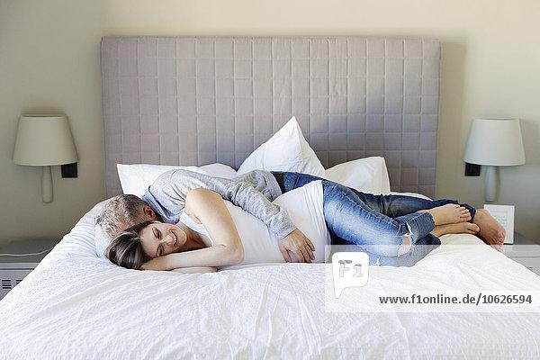 Mann und schwangere Frau kuscheln auf dem Bett