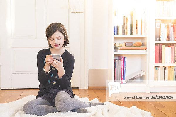 Portrait of girl sitting on blanket on the floor using smartphone