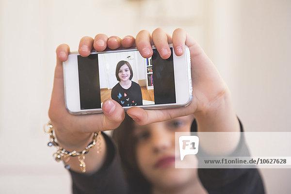 Mädchenhände zeigen Smartphone mit Selbstfotografie