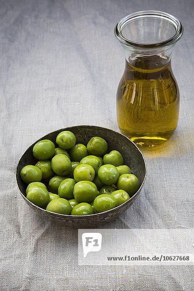 Schale mit grünen Oliven und Karaffe mit Olivenöl