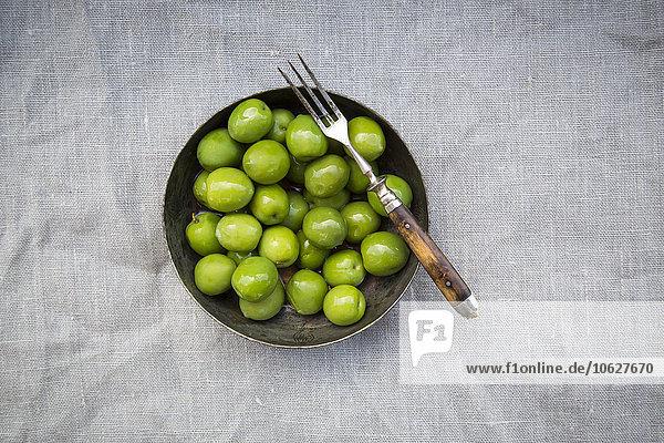 Schale mit grünen Oliven und einer Gabel