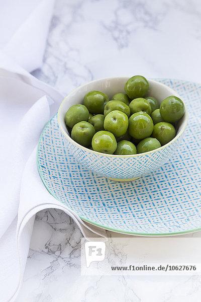 Schale mit grünen Oliven auf Teller und weißem Marmor