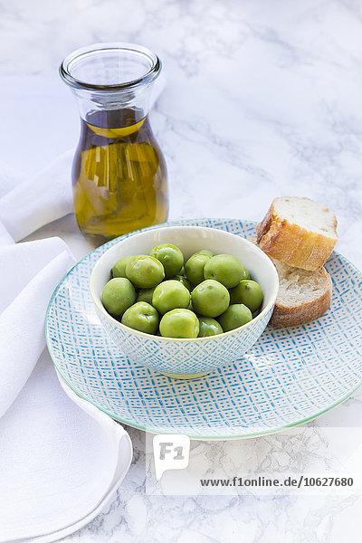 Schale mit grünen Oliven  Brotscheiben und Karaffe mit Olivenöl