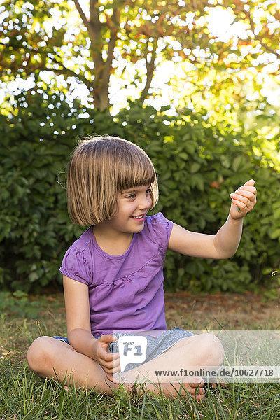 Lächelndes kleines Mädchen  das auf einer Wiese sitzt und etwas in der Hand hält.