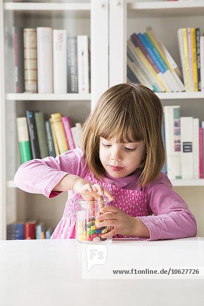 Portrait of little girl taking jelly bean