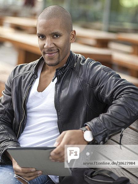 Deutschland  Köln  Junger Mann auf Bank sitzend mit digitalem Tablett