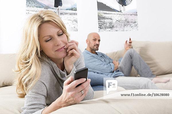 Reife Paare  die auf dem Sofa sitzen und ihre Smartphones benutzen.