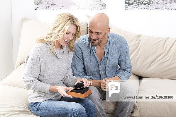 Ein reifer Mann  der seiner Frau ein Geschenk macht.