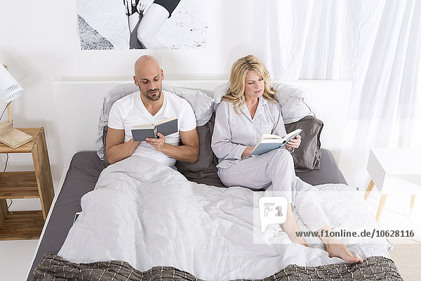 Reife Paare lesen im Bett