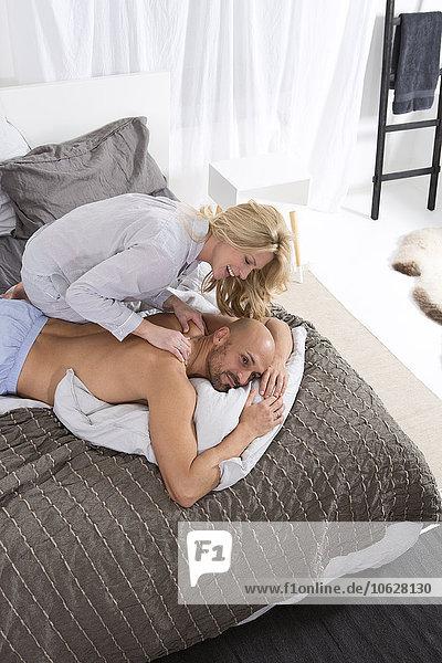 Glückliches Paar im Schlafzimmer  Frau gibt dem Mann eine Rückenmassage