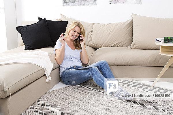 Lächelnde Frau sitzt auf dem Boden ihres Wohnzimmers und telefoniert.