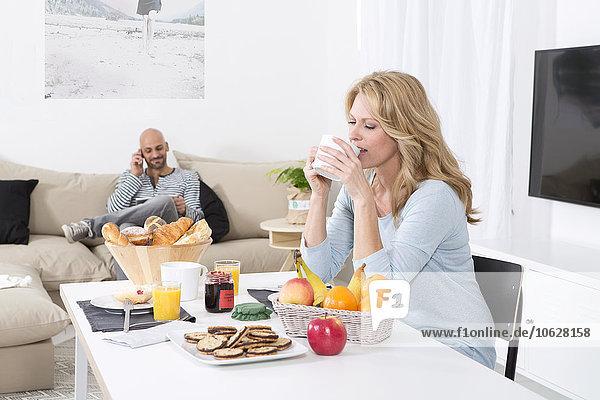 Reife Frau beim Frühstück  während der Mann am Telefon spricht.