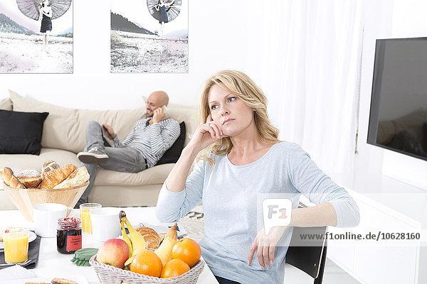 Reife Frau wartet frustriert am Frühstückstisch auf den Mann