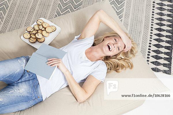 Porträt einer lachenden blonden Frau auf der Couch liegend mit Buch und Keksteller