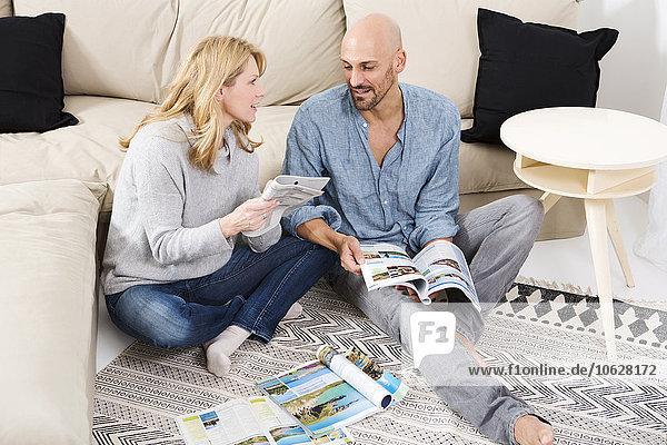 Ein Paar sitzt auf dem Boden seines Wohnzimmers und schaut sich Reisekataloge an.