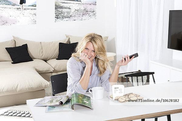 Porträt einer lächelnden Frau  die in ihrem Wohnzimmer mit Zeitschriften und Keksen am Tisch sitzt.