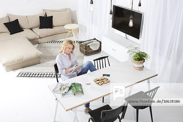 Lächelnde Frau sitzt am Tisch in ihrem Wohnzimmer mit Hilfe eines digitalen Tabletts.