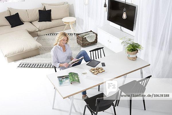 Lächelnde Frau sitzt am Tisch in ihrem Wohnzimmer und liest Magazin.