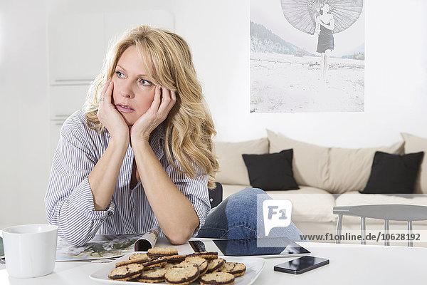 Frau sitzt am Tisch in ihrem Wohnzimmer mit den Händen im Kopf.