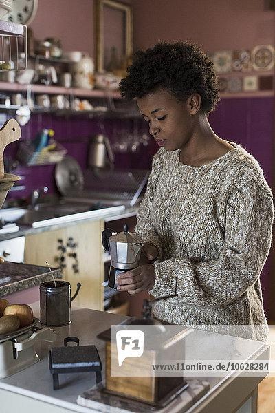 Junge Frau in der Küche beim Kaffeezubereiten