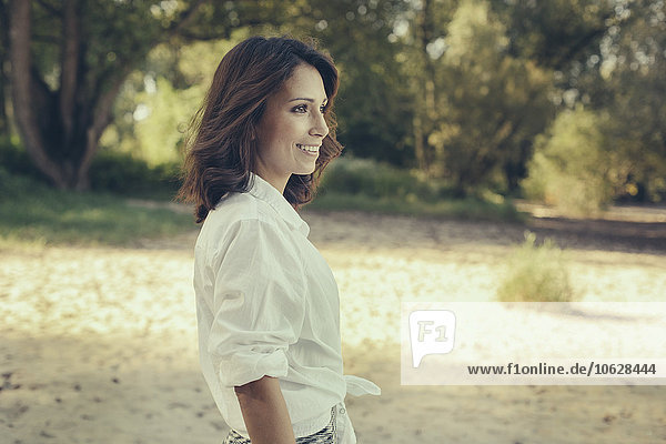 Porträt einer lächelnden Frau  die in die Ferne blickt