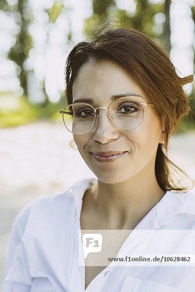 Porträt einer lächelnden Frau mit braunen Haaren und Brille