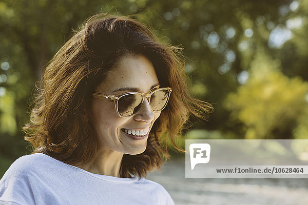Portrait of smiling woman with brown hair wearing sunglasses
