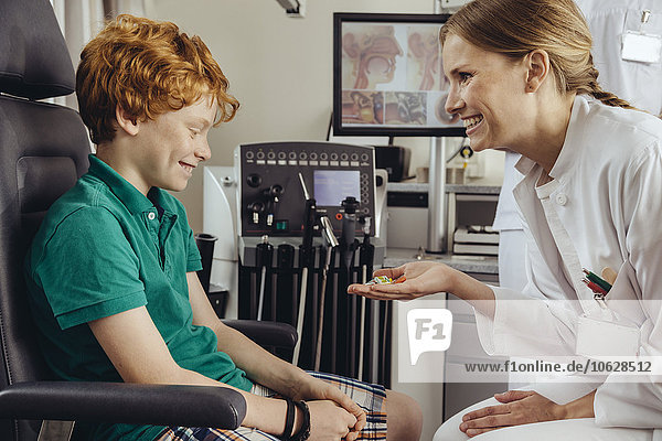 Ärztin  die nach erfolgreichem Screening in der HNO-Praxis Kinderbonbons verabreicht.
