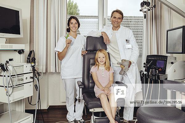 Arzt und Krankenschwester in der Praxis mit kleinem Mädchen im HNO-Stuhl