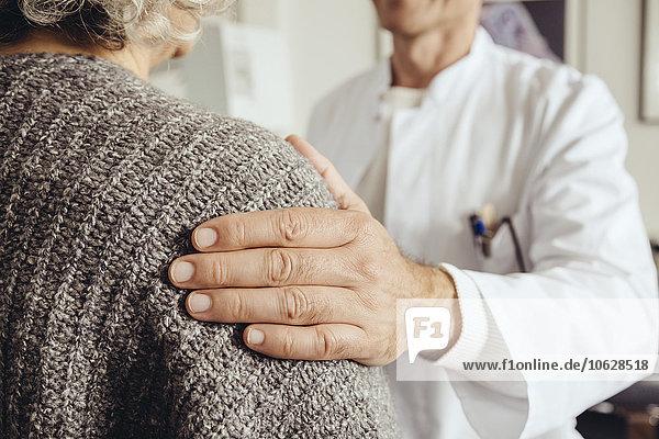 Arzt beruhigt ältere Patientin
